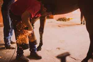 man holding lighting tool near brown horse